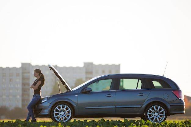 Jonge aantrekkelijke vrouw bij auto met open kap in groene weide op wazig flatgebouw