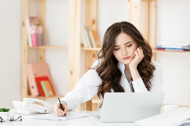 Jonge aantrekkelijke vrouw bij een modern bureau dat met laptop werkt en aan iets denkt