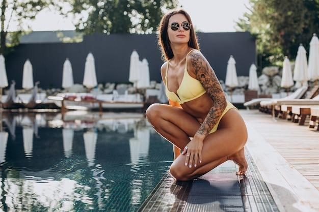 Jonge aantrekkelijke vrouw bij het zwembad