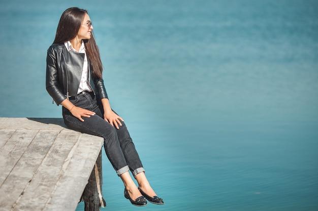 Jonge aantrekkelijke vrouw buitenshuis. mooie vrouw op een overzeese achtergrond in de herfst tijd