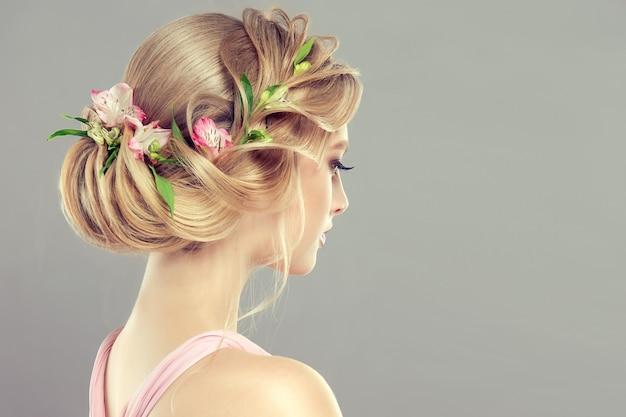 Jonge, aantrekkelijke vrouw demonstreert blond haar verzameld in elegant kapsel met verse bloemen erin. kapperskunst en haarkleuring. uitzicht vanaf achterkant.