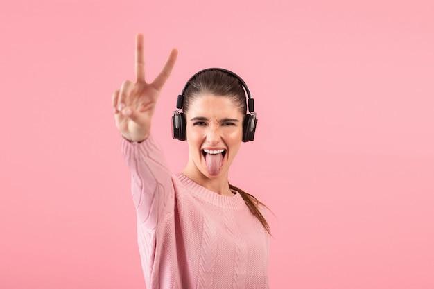 Jonge aantrekkelijke vrouw die aan muziek in draadloze hoofdtelefoons luistert die het roze sweater glimlachen dragen