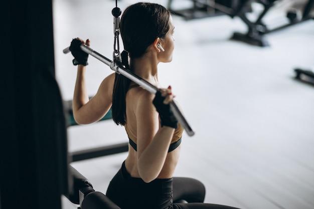 Jonge aantrekkelijke vrouw die bij de gymnastiek uitoefent