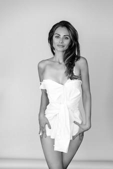 Jonge aantrekkelijke vrouw die een korte witte kleding draagt