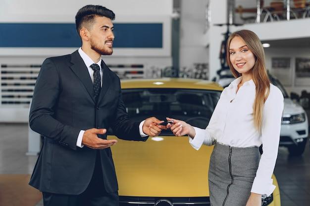 Jonge aantrekkelijke vrouw die een nieuwe auto in autosalon koopt dicht omhoog