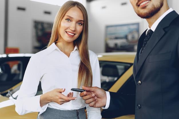 Jonge aantrekkelijke vrouw die een nieuwe auto in autosalon koopt