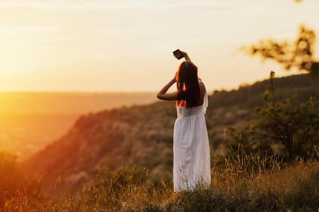 Jonge aantrekkelijke vrouw die een smartphone houdt en een selfie op de heuvel neemt