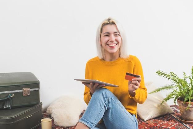 Jonge aantrekkelijke vrouw die haar creditcard gebruiken om een online aankoop met een digitale touchscreen tablet thuis te doen.