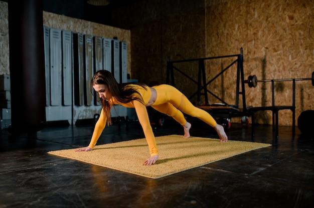 Jonge aantrekkelijke vrouw die lichaamsgewichtfitness training uitvoert in haar appartement mooie vrouw doet plank oefening. slank fitnessmeisje in de moderne flat.