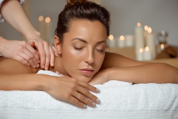 Jonge aantrekkelijke vrouw die massage het ontspannen in kuuroordsalon heeft.