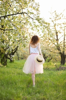 Jonge aantrekkelijke vrouw die met krullend haar in een groen gebloeide tuin loopt. lente romantische sfeer