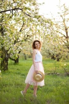 Jonge aantrekkelijke vrouw die met krullend haar in een groen gebloemde tuin loopt. lente gevoel