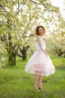 Jonge aantrekkelijke vrouw die met krullend haar in een groen gebloemde tuin loopt. lente romantische stemming