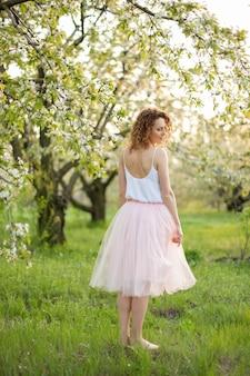 Jonge aantrekkelijke vrouw die met krullend haar in een groen gebloemde tuin loopt