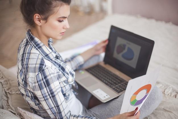 Jonge aantrekkelijke vrouw die naar huis bij laptop werkt
