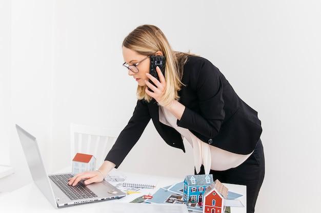Jonge aantrekkelijke vrouw die op cellphone spreekt terwijl het werken aan laptop in onroerende goederenbureau