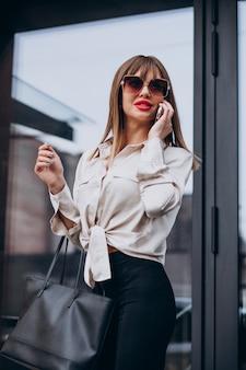 Jonge aantrekkelijke vrouw die op de telefoon spreekt