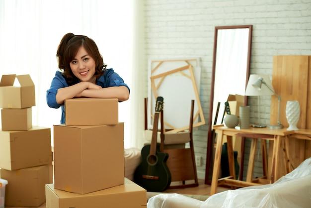 Jonge aantrekkelijke vrouw die op een stapel van pakketdozen het glimlachen leunt