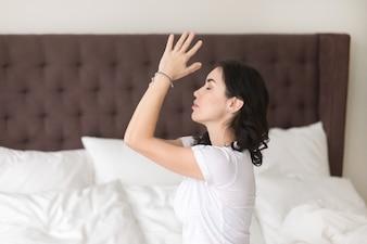 Jonge aantrekkelijke vrouw die op het bed, profiel mediteren