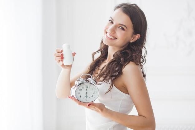 Jonge aantrekkelijke vrouw die pillen op het juiste moment neemt