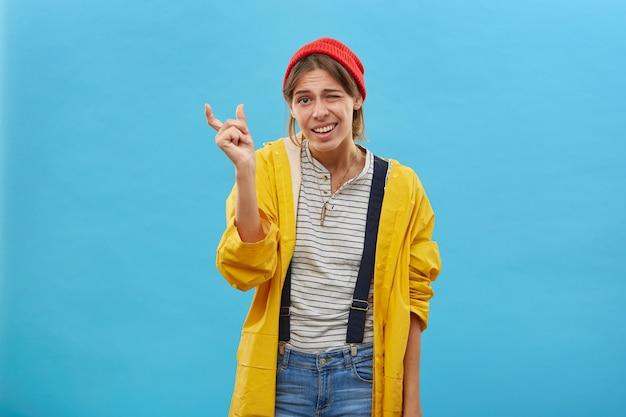 Jonge aantrekkelijke vrouw die rode hoed, gele jas en jean-overall draagt die tijdens het gebaren iets heel kleins met handen toont. vissersvrouw die de grootte van de vis aantoont
