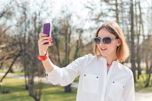 Jonge aantrekkelijke vrouw die selfie foto op smartphone maken