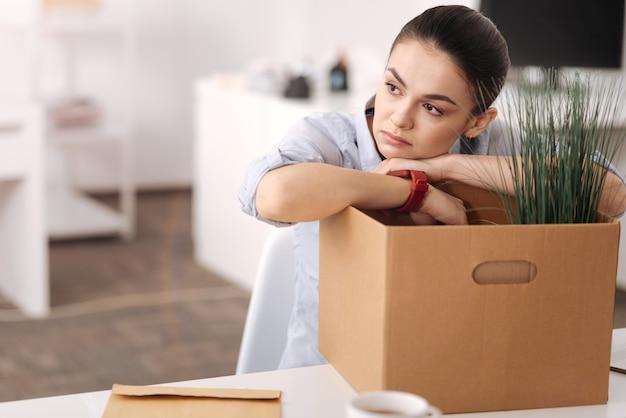 Jonge aantrekkelijke vrouw die slimme horloges draagt die wapens op de doos zetten terwijl zij in bureau is