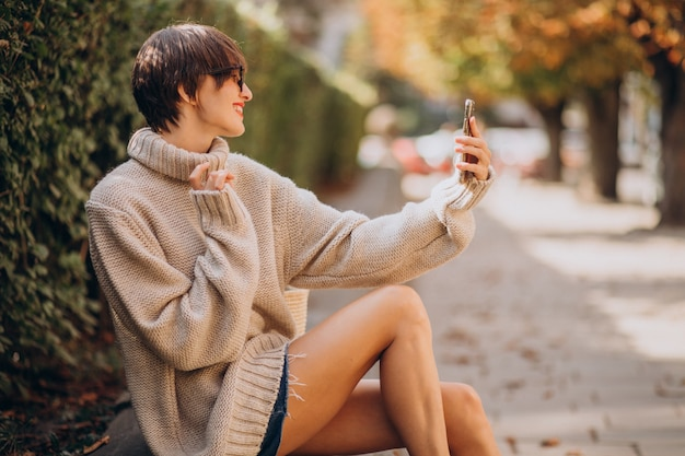 Jonge aantrekkelijke vrouw die telefoon met behulp van