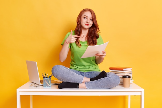Jonge aantrekkelijke vrouw die witboek toont en met wijsvinger aangeeft