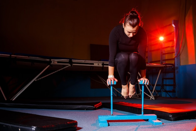 Jonge aantrekkelijke vrouw die yoga beoefent, in de hand staat, balansoefening, handstand, training, in sportkleding, zwarte legging en top, binnenshuis in volle groei