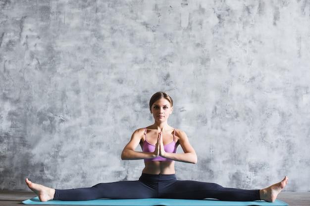 Jonge aantrekkelijke vrouw die yoga binnenshuis beoefent