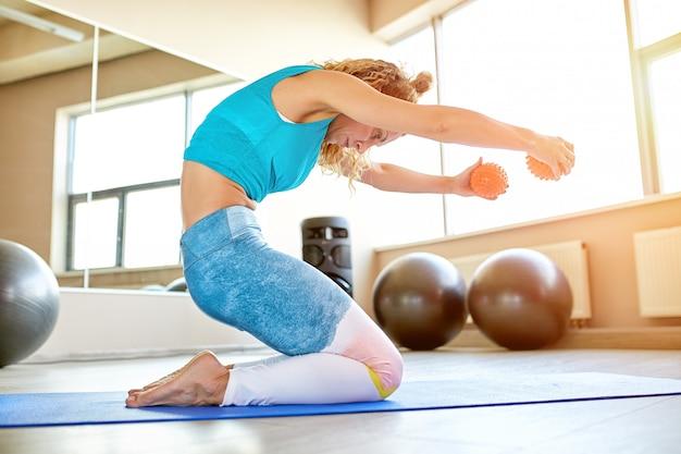 Jonge aantrekkelijke vrouw die yoga in fitnessruimte doet.