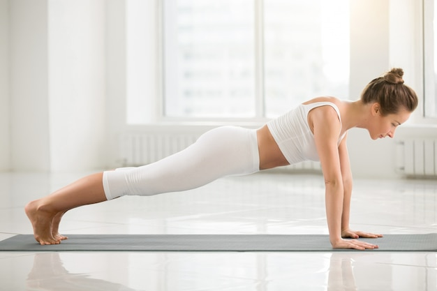 Jonge aantrekkelijke vrouw die zich in plank bevindt zich, witte kleur backg