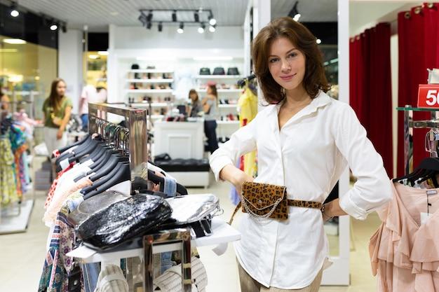 Jonge aantrekkelijke vrouw die zich met handen op haar heupen bevindt die op modieus taillepak proberen.