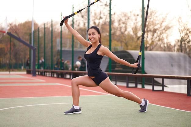 Jonge aantrekkelijke vrouw doet schorsing training met fitness bandjes buitenshuis