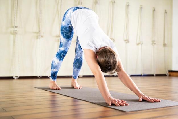 Jonge aantrekkelijke vrouw doet yoga oefening in de sportschool op mat