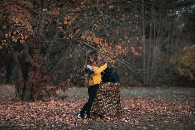 Jonge aantrekkelijke vrouw en schattige tiener meisje tijd samen doorbrengen in herfst park. kopieer ruimte.