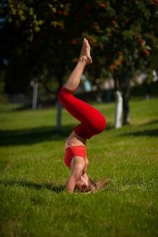 Jonge aantrekkelijke vrouw het beoefenen van yoga buitenshuis. het meisje voert een handstand ondersteboven uit