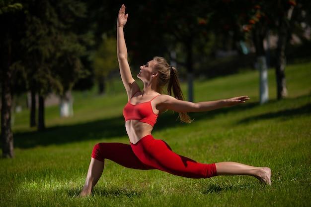 Jonge aantrekkelijke vrouw het beoefenen van yoga buitenshuis. het meisje voert verschillende oefeningen op het gras uit