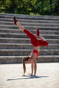 Jonge aantrekkelijke vrouw het praktizeren yoga in openlucht. het meisje voert een handstand ondersteboven