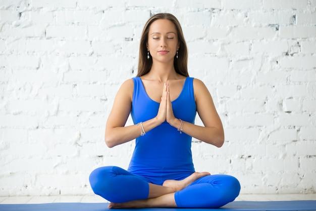 Jonge aantrekkelijke vrouw in ardha padmasana pose, witte studio bac