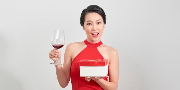 Jonge aantrekkelijke vrouw in avondjurk met geschenken rode dozen op witte achtergrond. nieuwjaar/verjaardag/jubileum, vakantieconcept, opwinding en bewondering
