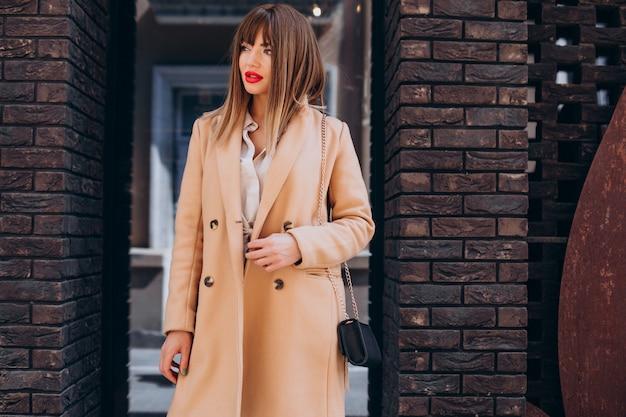 Jonge aantrekkelijke vrouw in beige jas poseren in de straat