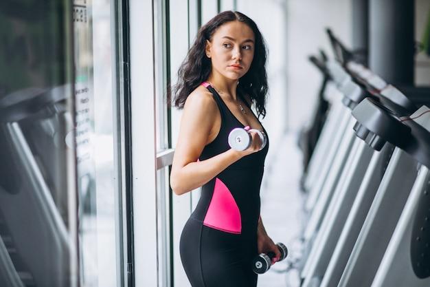 Jonge aantrekkelijke vrouw in de sportschool met halters