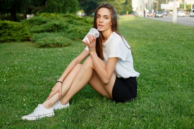Jonge aantrekkelijke vrouw in een wit t-shirt een milkshake drinken op het gras