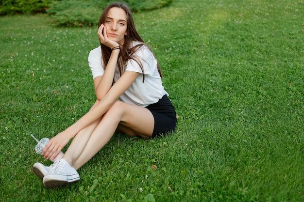 Jonge aantrekkelijke vrouw in een wit t-shirt zittend op het gras