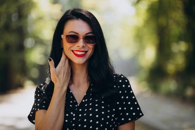 Jonge aantrekkelijke vrouw in elegante kleding die zich in bos bevindt