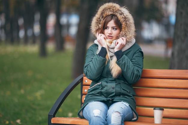Jonge aantrekkelijke vrouw in herfstkleren zit op een bankje in een stadspark. de vrouw is gekleed in een stijlvol jasje met bont. herfst tijd.