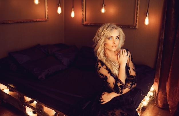 Jonge aantrekkelijke vrouw in het zwarte negligé stellen op bed