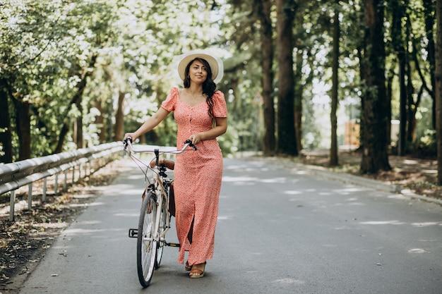 Jonge aantrekkelijke vrouw in kleding berijdende fiets